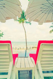 Beautiful beach chairs with umbrella around outdoor swimming poo Royalty Free Stock Photo