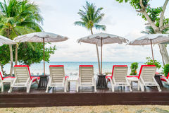 Beautiful beach chairs with umbrella around outdoor swimming Royalty Free Stock Images