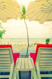 Beautiful beach chairs with umbrella around outdoor swimming Royalty Free Stock Photography