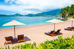 Beautiful beach with chaise lounges in Montenegro. Beautiful beach with chaise lounges in Sveti Stefan near Budva, Montenegro. Luxury resort at Adriatic sea stock images
