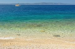 Beautiful beach with clear water in front and ship and island Hvar in background Royalty Free Stock Photo