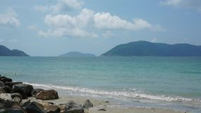 Beautiful beach of Con Dao, Vietnam. Gentle waves splashing water on the seashore, some clouds in the blue sunny sky stock footage