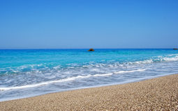 Waves the big blue sea. Beautiful beach with crystal clear blue sea,and interesting small stones,Greece Royalty Free Stock Image