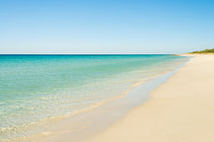 Beautiful beach with golden sand and clear water Stock Photos