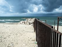 A beautiful beach invaded by waste. Produced by humans, while a storm approaches threatening royalty free stock images