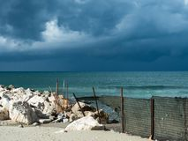A beautiful beach invaded by waste. Produced by humans, while a storm approaches threatening royalty free stock image
