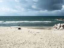 A beautiful beach invaded by waste. Produced by humans, while a storm approaches threatening stock photos