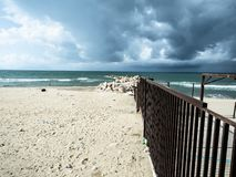 A beautiful beach invaded by waste. Produced by humans, while a storm approaches threatening stock image