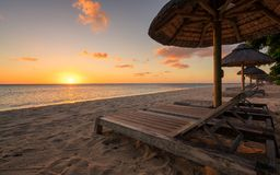 Awesome sunset beach at Mauritius. Beautiful beach at Mauritius island with wooden parasol in the right side, amazing sunset Royalty Free Stock Image