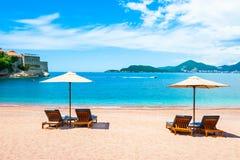 Beautiful beach in Montenegro. Beautiful beach with chaise lounges and umbrellas in Sveti Stefan near Budva, Montenegro. Luxury resort at Adriatic sea. Famous stock photo