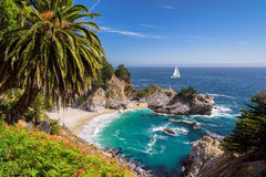 Beautiful beach with palm trees and the white yacht on the horizon. Fine beach and falls, Pacific coast, Julia Pfeiffer beach, Big Sur. California, USA Stock Image