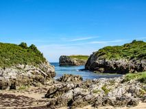 Beautiful beach Playa de Buelna with blue ocean water, rocky cliffs covered with green vegetation and blue sky in background stock photos