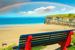 Beautiful beach with rainbow in ballybunion. Cliff walk bench overlooking the beautiful beach with rainbow in ballybunion Stock Photo