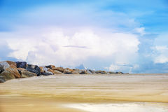 Beautiful  beach with rock dam and bright cloudy sky Royalty Free Stock Image