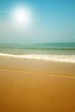 Beautiful beach with sand, blue waves and sky Stock Photo