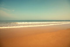 Beautiful beach with sand, blue waves and sky Stock Image
