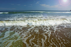 Beautiful beach, on the sand roll frothy waves. Fluffy waves on the shore Stock Photo