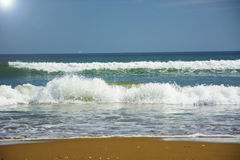 Beautiful beach, on the sand roll frothy waves. Fluffy waves on the shore Stock Images
