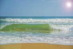 Beautiful beach, on the sand roll frothy waves. Fluffy waves on the shore Stock Photos
