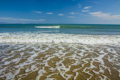 Beautiful beach, on the sand roll frothy waves. Fluffy waves on the shore Stock Image