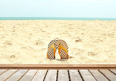 Beautiful beach with sandal and wooden floor background (summer concept). Royalty Free Stock Image