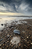 Beautiful beach scene full of pebbles in the coastline, natural circle formation in the sand Stock Photo