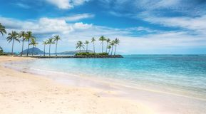 Tropical paradise in Honolulu, Hawaii, USA. A beautiful beach scene in the Kahala area of Honolulu, with fine white sand, shallow turquoise water, a view of royalty free stock photo