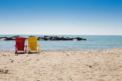 Beach scene with two colorful adirondack chairs Royalty Free Stock Photo