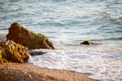 Beautiful beach with small pebbles and several large boulders Royalty Free Stock Image