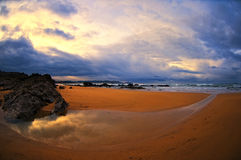 Beautiful beach in Spain, Asturias. Sunset in the beach with clouds and stormy weather Royalty Free Stock Photo
