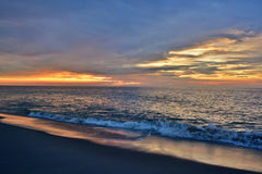 Beautiful Beach Sunrise. The sunrises over the ocean on a summer morning at the beach Stock Image