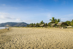 Beautiful beach and tropical beach cottage. The beach of Puerto Lopez in Ecuador in a sunny day. Tropical cottage can be seen in the back and the mountains Royalty Free Stock Images