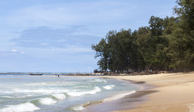 Beautiful beach with tropical trees with a wave of the sea and blue sky with white clouds. Thailand. Phuket. Stock Photography