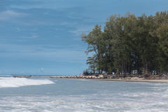 Beautiful beach with tropical trees with a wave of the sea and blue sky with white clouds. Thailand. Phuket. Stock Images