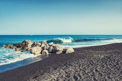 Beautiful beach with turquoise water and black sand. Stock Images