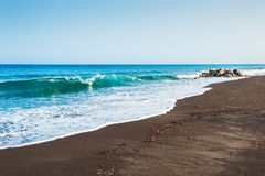 Beautiful beach with turquoise water and black volcanic sand Stock Photos