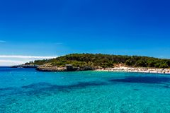 Beautiful beach with turquoise water crowded with tourists in Cala Mondrago, Mallorca. Spain Royalty Free Stock Images