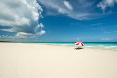 Red parasol on the Caribbean beach. Beautiful beach of Varadero during a sunny day, fine white sand and turquoise and green Caribbean sea,on the right one red royalty free stock photos