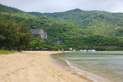 Beautiful beach of Vietnam is surrounded by mountains. Yellow sand, clear sea water, away vacationers people, ships, mountains covered with greenery, Paradise Royalty Free Stock Image