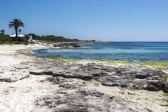 Beautiful beach with white sand, palm trees and granite rocks, blue Mediterranean Sea, simplyt paradise, Menorca, Spain. NThe beautiful landscape of the deserted Royalty Free Stock Image