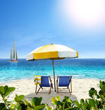 Beautiful beach with white sand, two chairs, umbrella and a sail. Beautiful beach with white sand, two chairs, white-yellow umbrella and a sailing boat in the Royalty Free Stock Photos
