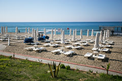 Beautiful beach with white sunbeds and umbrellas. With blue sea pier Stock Photography