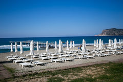 Beautiful beach with white sunbeds and umbrellas. With blue sea pier  and Alanya castle rock on background Royalty Free Stock Images
