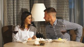 A beautiful bearded man gives a gift to his girlfriend in a restaurant. Happiness,love, surprise. First date. Valentine`s day stock video footage