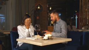 A beautiful bearded man gives a gift to his girlfriend in a restaurant. Happiness,love, surprise. First date. Valentine`s day stock video