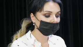 Beautiful beautician in a black medical mask makes the procedure her client. Close-up view of a woman`s face with stock video footage