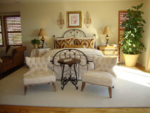 Beautiful  Bed Room. Beautiful bed room very light and bright white rug on wood floors two chairs and a table at end of bed Stock Images