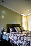 Beautiful bedroom with curtains on the wall and cushions Royalty Free Stock Images
