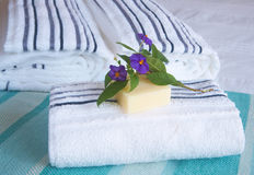 Beautiful bedroom interior. With white sheets and striped towels with soap and flowers Stock Image