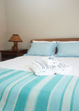 Beautiful bedroom interior. With white sheets and striped towels Stock Photography